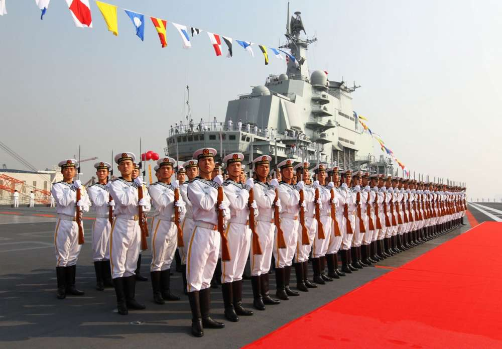"""Naval honour guards stand as they wait for a review on China's aircraft carrier """"Liaoning"""" in Dalian, Liaoning province"""